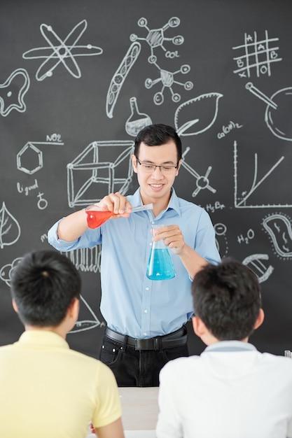 Glücklicher vietnamesischer chemielehrer, der rote und blaue flüssigkeiten vor den schülern mischt, wenn er die doppelte ersatzreaktion erklärt Premium Fotos