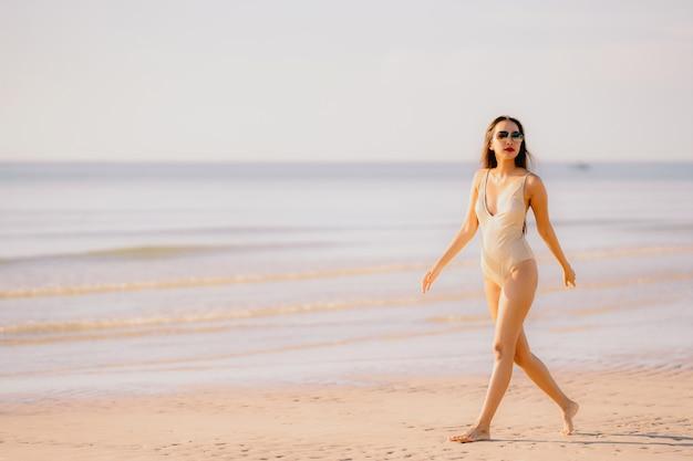 Glücklicher weg des schönen jungen asiatischen frauenlächelns des porträts auf dem tropischen naturstrandmeer im freien Kostenlose Fotos