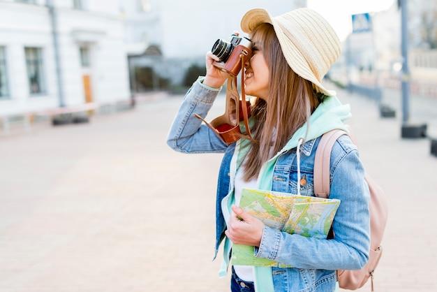 Glücklicher weiblicher reisender, der in der hand die karte anklickt das foto auf kamera hält Kostenlose Fotos