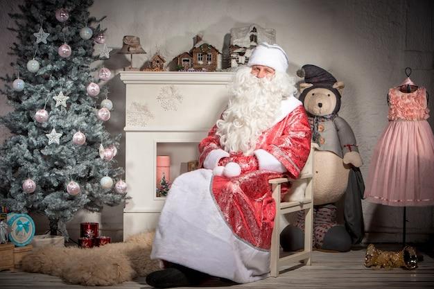 Glücklicher weihnachtsmann, der auf der weihnachtsdekoration sitzt Kostenlose Fotos