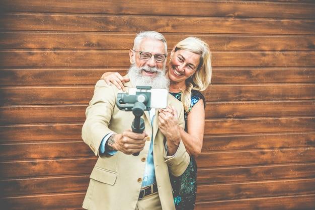 Glückliches älteres paar, das spaß macht, video mit smartphone zu machen Premium Fotos