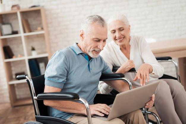 Glückliches älteres paar in den rollstühlen betrachtet laptopschirm. Premium Fotos