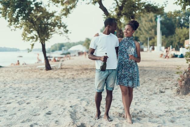 Glückliches afroamerikanisches paar steht auf sandy river beach still. Premium Fotos
