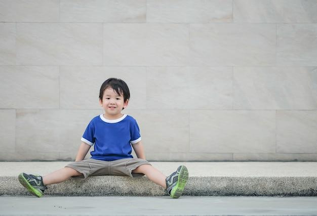 Glückliches asiatisches kind der nahaufnahme mit lächelngesicht sitzen an der bahn auf strukturiertem hintergrund der marmorsteinwand mit kopienraum Premium Fotos