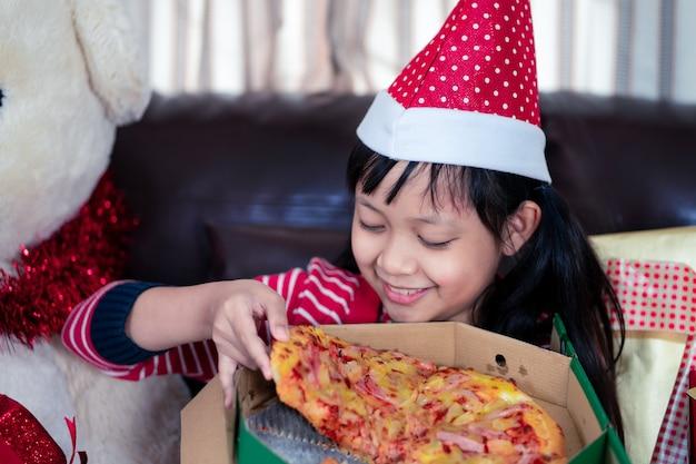 Glückliches asiatisches kindermädchen, das pizza in dem raum isst, der für weihnachten verziert wird Premium Fotos