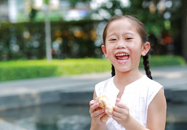 Glückliches asiatisches kleines mädchen, das brot mit angefüllter erdbeere isst Premium Fotos