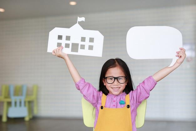 Glückliches asiatisches kleines mädchen in den rosa-gelben jeansstoffen, die modellpapierschule und leere leere spracheblase halten, um etwas im klassenzimmer mit dem schauen gerade zu erklären. bildungs- und gesprächskonzept. Premium Fotos