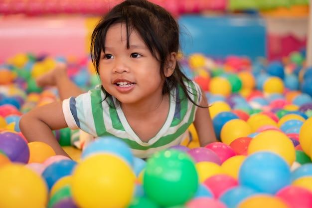 Glückliches asiatisches mädchen (4 jahre alt), das kleine bunte bälle in der poolkugel spielt. das spielen ist das beste lernen für kinder. Premium Fotos