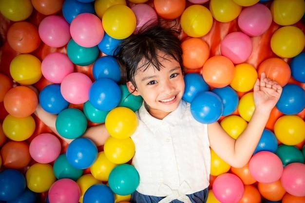 Glückliches asiatisches mädchen, das im bunten ballpool spielt Premium Fotos
