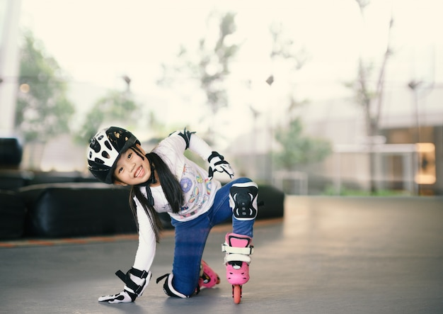 Glückliches asiatisches mädchen, das zum rollschuh lernt. kinder mit schutzpolstern für eine sichere fahrt. Premium Fotos