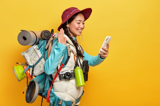 Glückliches asiatisches mädchen winkt palme, begrüßt jemanden per videoanruf, hält handy in der hand, trägt rucksack mit allen notwendigen dingen, hat wandertour, isoliert über gelbe wand Kostenlose Fotos
