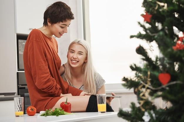 Glückliches attraktives blondes mädchen, das tablette hält und in die kamera lächelt, während sie neben ihrer schönen freundin in der küche nahe weihnachtsbaum sitzt. frauen lachen über artikel, die sie per gadget lesen. Kostenlose Fotos