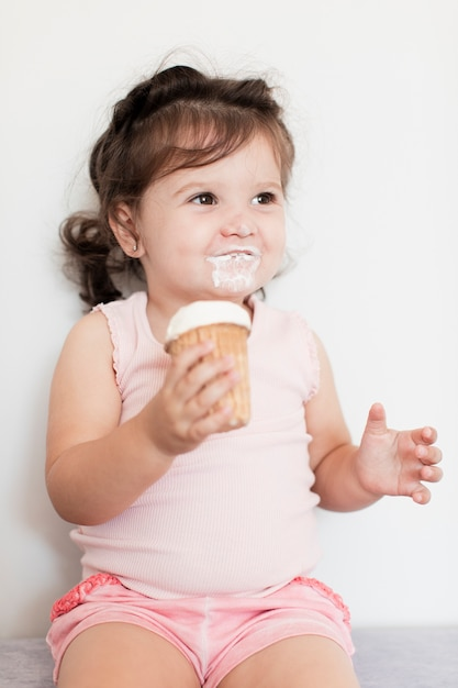 Glückliches baby, das eine eiscreme isst Kostenlose Fotos