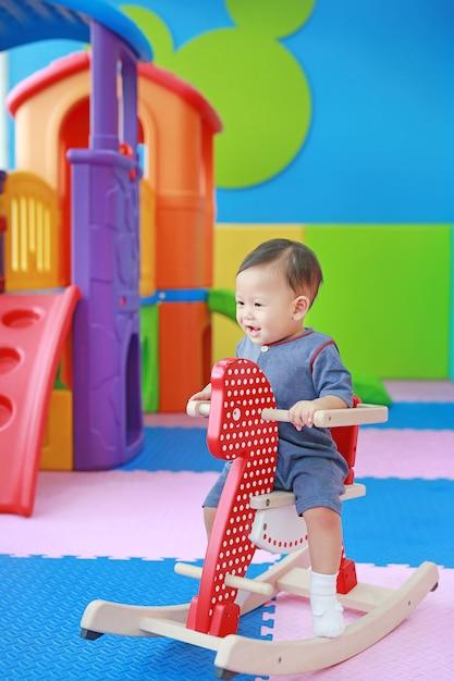 Glückliches baby, das pferd auf spielplatz, hölzernes schaukeln spielt. Premium Fotos