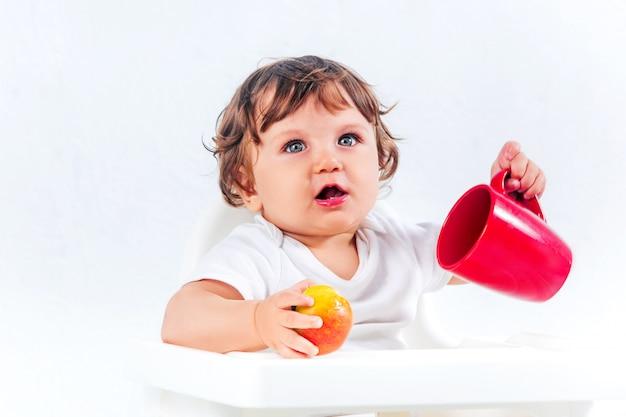 Glückliches baby, das sitzt und isst Kostenlose Fotos