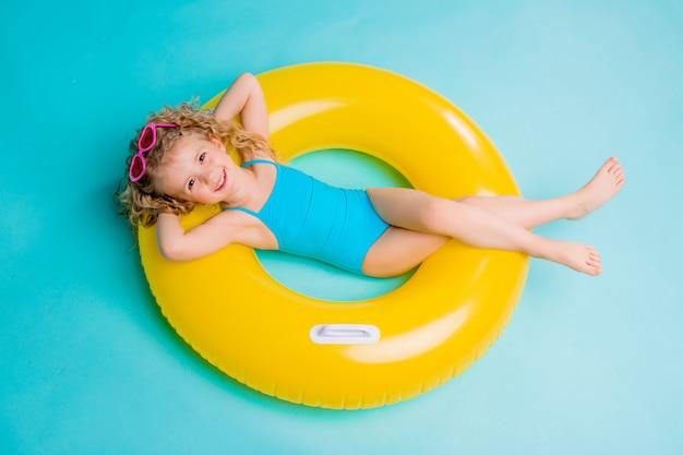 Glückliches baby im badeanzug mit dem kreis lokalisiert auf blauem hintergrund Premium Fotos