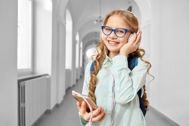 Glückliches blondes schulmädchen, das musik von kopfhörern hört Premium Fotos