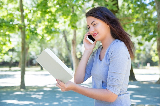 Glückliches buch junger dame leseund um telefon im park ersuchend Kostenlose Fotos