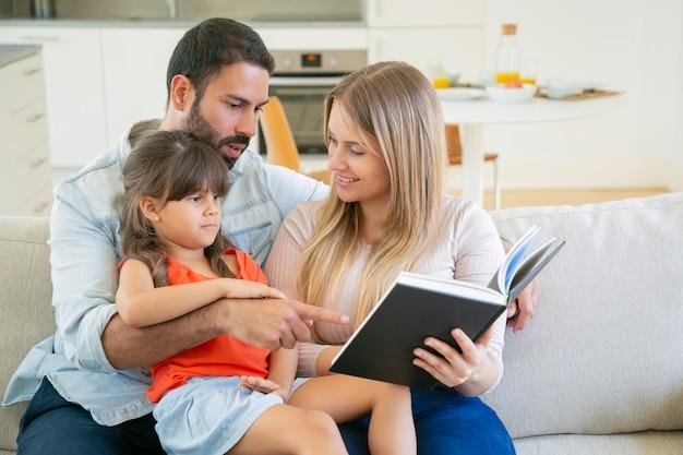Glückliches elternpaar und kleines schwarzhaariges mädchen, das auf couch im wohnzimmer sitzt und buch zusammen liest. Kostenlose Fotos