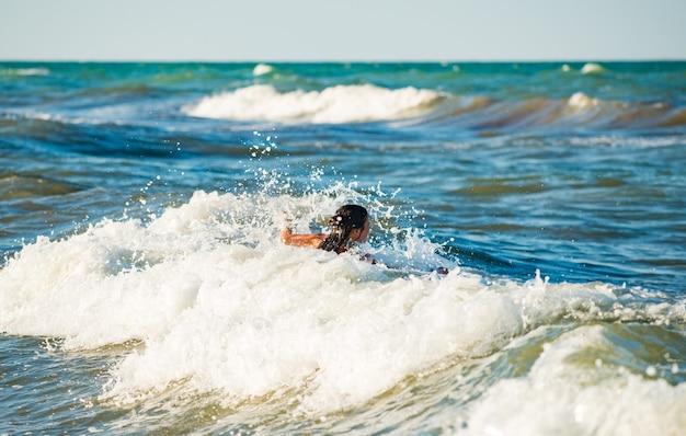 Glückliches emotionales kleines mädchen badet in den schaumigen stürmischen meereswellen an einem sonnigen warmen sommertag Premium Fotos