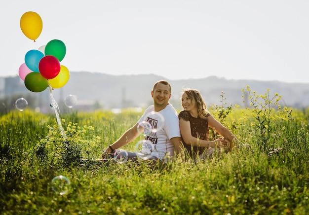 Glückliches erwachsenes paar hat spaß auf einem grünen feld, das mit bunten ballonen sitzt Kostenlose Fotos