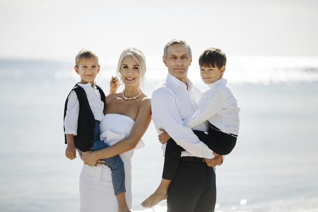 Glückliches familienporträt am sonnigen tag mit zwei jugendlichen söhnen, die auf den händen der eltern sitzen Kostenlose Fotos