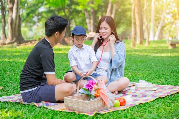 Glückliches feiertagspicknickmoment-spielrolle der asiatischen jugendlich kinderfamilie eins als doktor im park. Premium Fotos