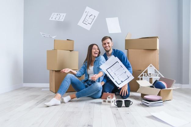 Glückliches fröhliches paar in der liebe, die spaß zusammen in ihrer eigenen neuen wohnung hat, nachdem auf den pappkartons entfernt Premium Fotos