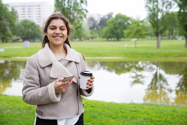 Glückliches frohes mädchen mit telefon kaffee zum mitnehmen genießend Kostenlose Fotos