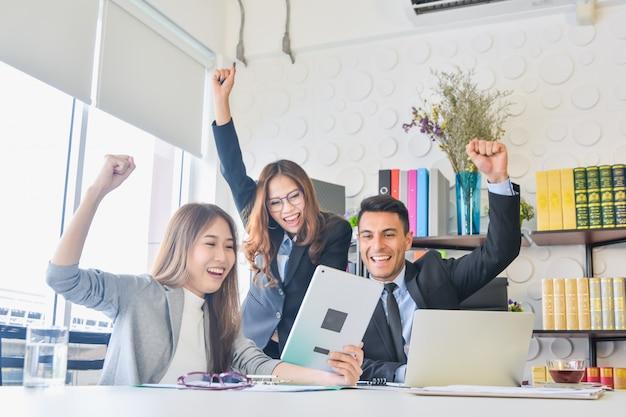Glückliches geschäftsteam mit dem arm angehoben in büro nach dem treffen des glücklichen erfolgs Premium Fotos