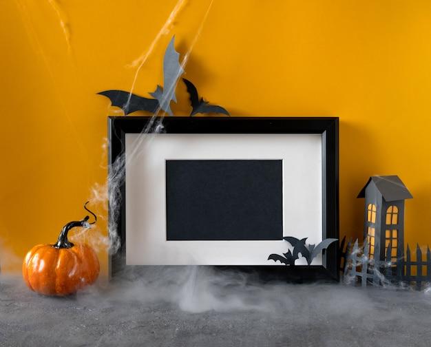 Glückliches halloween-feiertagskonzept. schwarzer rahmen auf orange hintergrund Premium Fotos