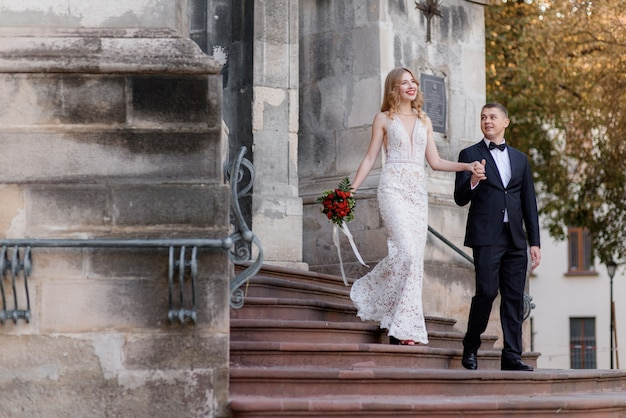 Glückliches hochzeitspaar kommt aus der kirche auf der treppe und hält sich an den händen Kostenlose Fotos