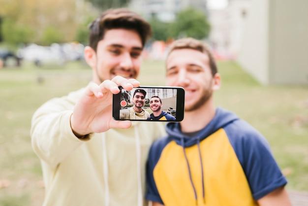 Glückliches homosexuelles paarschießen selfie auf straße Kostenlose Fotos