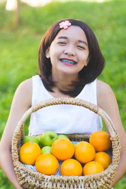 Glückliches junges asiatisches mädchen halten orange korb im garten. Premium Fotos