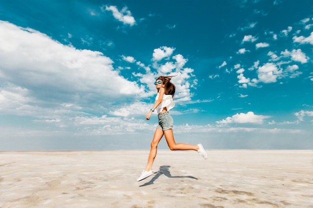 Glückliches junges frisches schlankes sportliches mädchen läuft in trendigen jeansshorts und weißen turnschuhen am strand entlang. blauer himmel in den wolken, sonnige sommerstimmung. Kostenlose Fotos