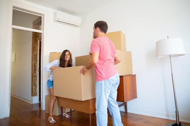 Glückliches junges hispanisches paar, das in neue wohnung zieht und kartonschachteln und möbel trägt Kostenlose Fotos