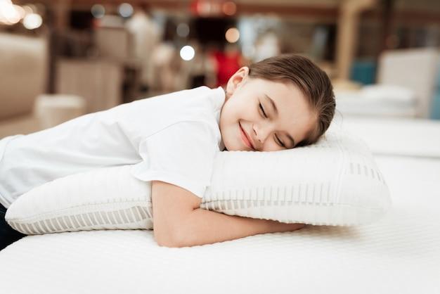 Glückliches junges mädchen, das mit kissen auf matratze schläft Premium Fotos