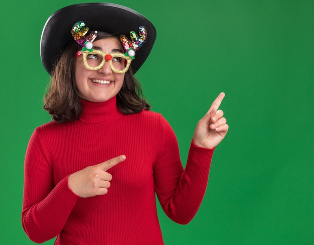 Glückliches junges mädchen im roten pullover, der lustige brille und schwarzen hut trägt, der oben schaut Kostenlose Fotos