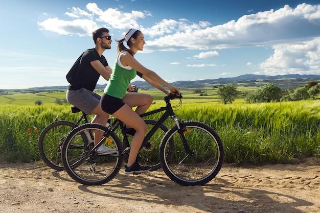 Glückliches junges paar auf einem fahrrad fahren auf dem land Premium Fotos