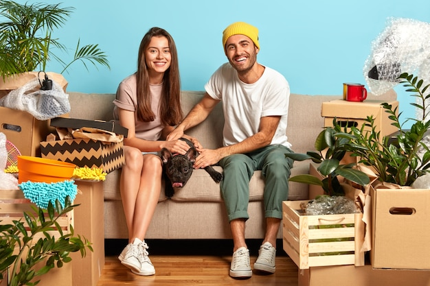 Glückliches junges paar, das auf der couch sitzt, umgeben von kisten Kostenlose Fotos
