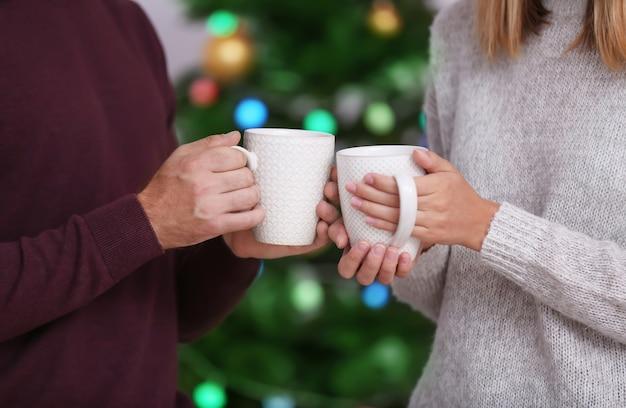 Glückliches junges paar, das heiße schokolade zu hause trinkt. weihnachtskonzept Premium Fotos