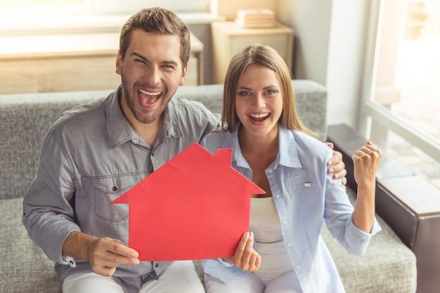 Glückliches junges paar hält ein papierhaus Premium Fotos