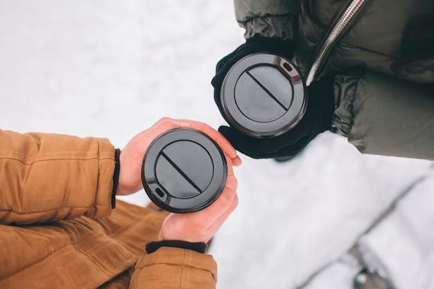 Glückliches junges paar im winter. familie draußen. mann und frau, die aufwärts schauen und lachen. liebe, spaß, jahreszeit und leute - gehend in winterpark. kaffee trinken. draufsicht, nahaufnahme Premium Fotos