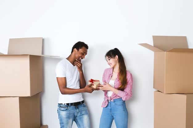 Glückliches junges paar in einer neuen wohnung. mann, der überraschungsgeschenk zur frau gegen ausgepackte kisten gibt. Premium Fotos