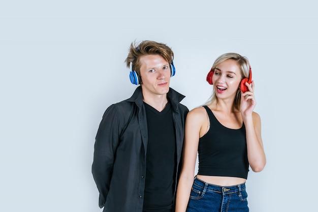 Glückliches junges paar in kopfhörer musik hören Kostenlose Fotos