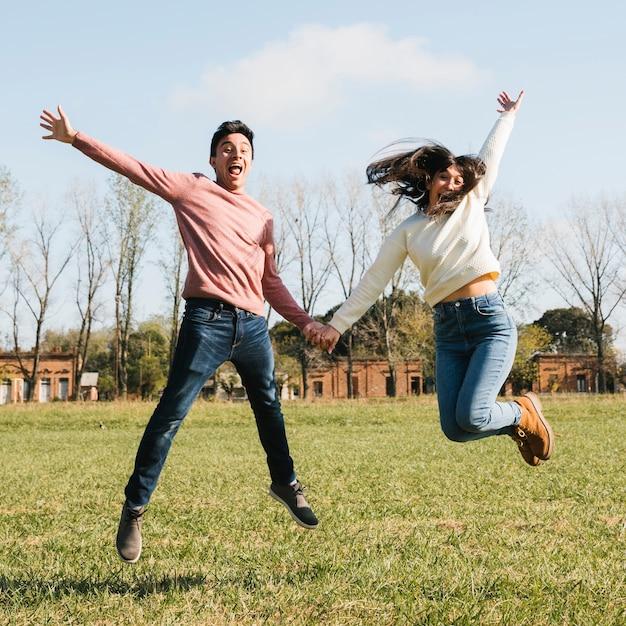 Glückliches junges paar springen Kostenlose Fotos