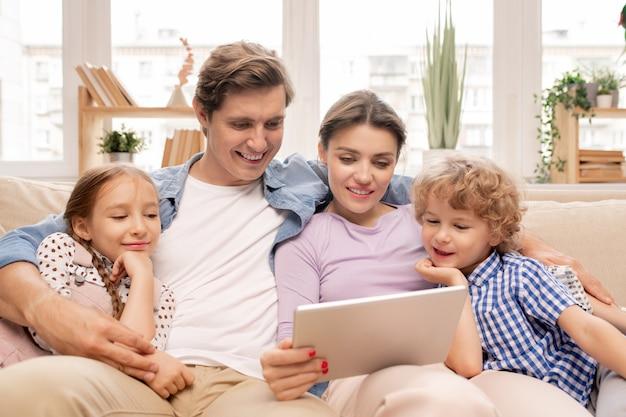 Glückliches junges paar und ihre zwei kinder in der freizeitkleidung, die zusammen auf der couch entspannen Premium Fotos