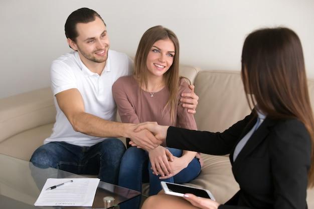 Glückliches junges paar- und vermittlermanagerhändeschütteln, nachdem vertrag unterzeichnet worden ist Kostenlose Fotos