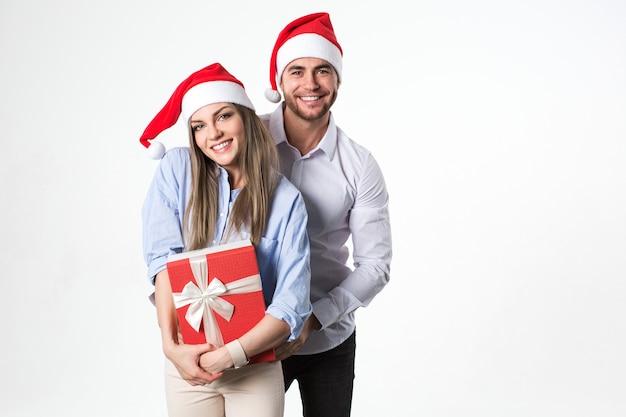 Glückliches junges weihnachtsferienpaar mit geschenk in der hand, lokalisiert über weißem hintergrund tragen weihnachtsmützen. Premium Fotos