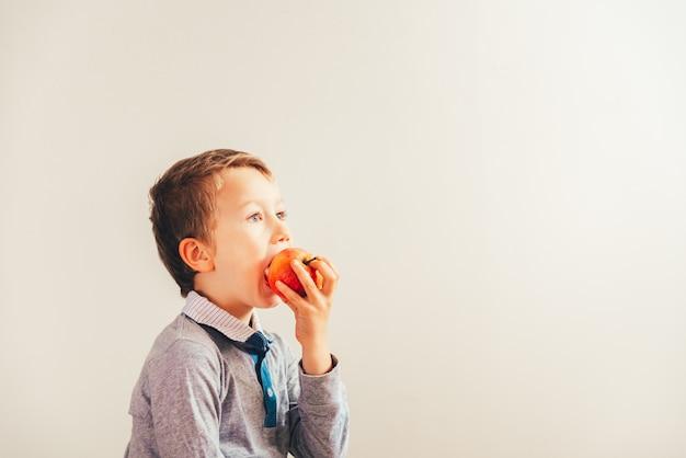 Glückliches kind, das einen apfel beißt, um sich für seine zähne zu interessieren und lokalisiert auf weißem hintergrund. Premium Fotos